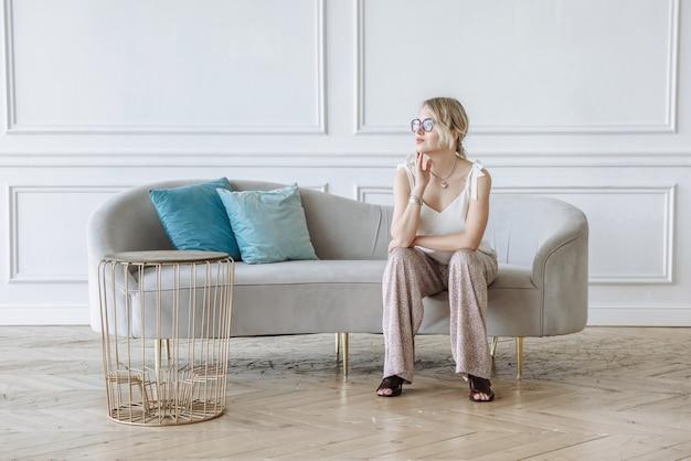 Frau sitzt auf einem sofa in einem schönen interieur