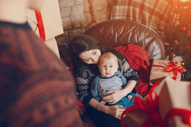 Frau sitzt auf einem sofa mit einem baby auf dem arm und mit einem berg von braunen geschenke mit roter schleife