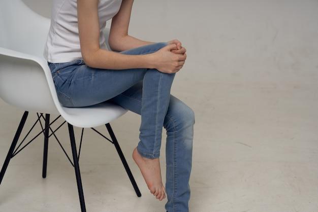 Frau sitzt auf einem stuhl beinverletzung gesundheitsprobleme. foto in hoher qualität