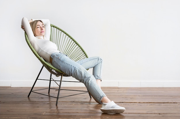 Frau sitzt auf einem stuhl long shot