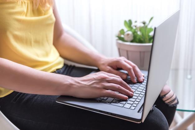 Frau sitzt auf einem stuhl mit einem laptop auf dem schoß