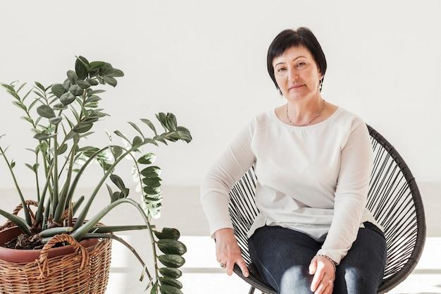 Frau sitzt auf einem stuhl neben pflanze
