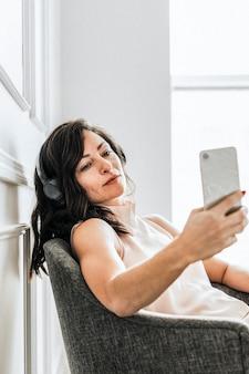 Frau sitzt auf einem stuhl und hört musik