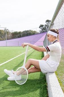 Frau sitzt auf einem tennisplatz
