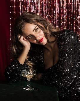 Frau sitzt auf einem tisch mit einem glas champagner