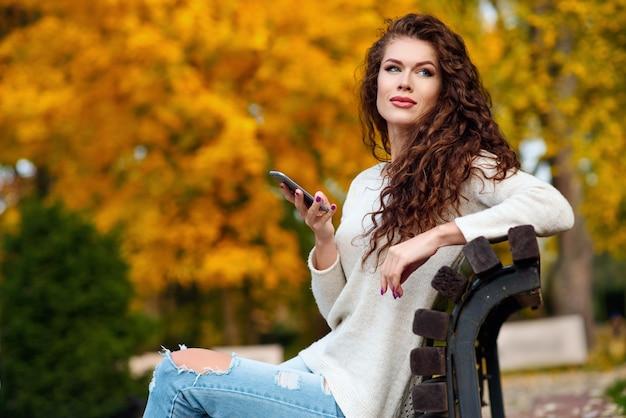 Frau sitzt auf einer bank im herbst im park und hält ein handy