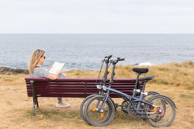 Frau sitzt auf einer bank vor dem meer und liest ein buch und zwei fahrräder, die sich gegen die bank lehnen