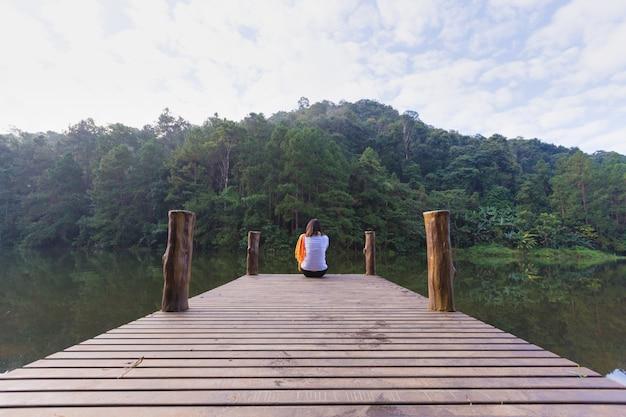 Frau sitzt auf einer holzbrücke