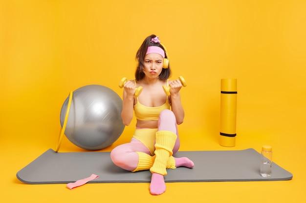 Frau sitzt auf fitnessmatte hält hanteln in activewear gekleidet benutzt sportgeräte sieht wütend aus hat training zu hause