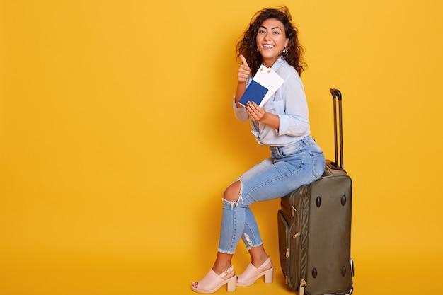 Frau sitzt auf grauer gepäcktasche vor dem gelben zeigen mit ihrem zeigefinger auf ticket in ihrer hand