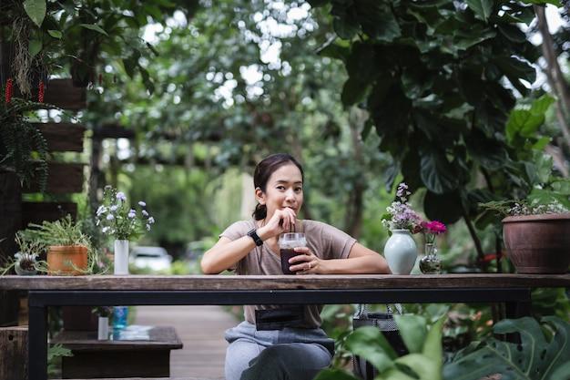 Frau sitzt auf holzstuhl, der eiskaffee im garten trinkt