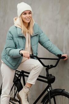 Frau sitzt auf ihrem fahrrad und lächelt