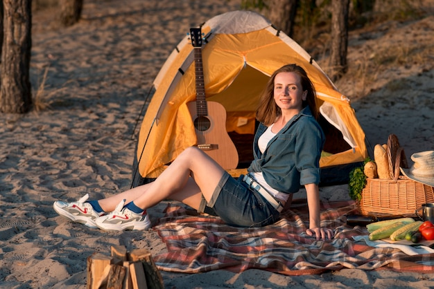 Frau sitzt auf picknickdecke