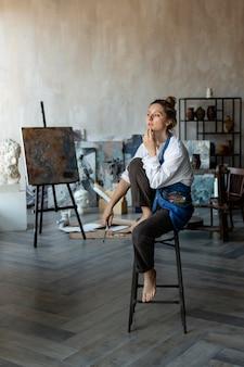 Frau sitzt auf stuhl und denkt nach