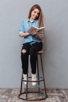 Frau sitzt auf stuhl und liest buch