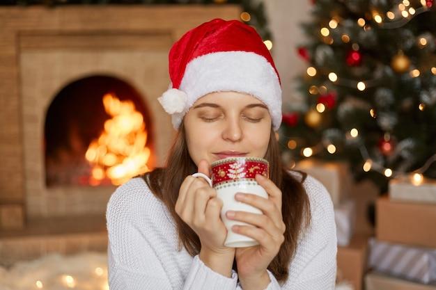 Frau sitzt im dekorierten wohnzimmer mit weihnachtsbaum und kamin