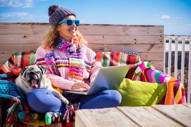 Frau sitzt im freien mit hund lächelt und genießt den besten freund - glückliche moderne menschen, die draußen mit laptop-computer und internetverbindung arbeiten - winterkleidung und farbenfroher stil