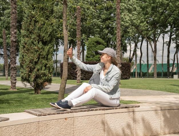 Frau sitzt im park im freien und macht selfie auf ihrem handy