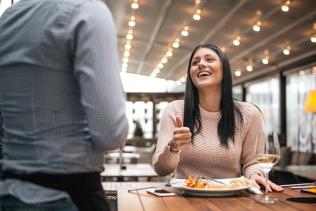 Frau sitzt im restaurant und zeigt daumen zum kellner.