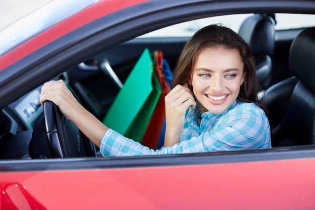 Frau sitzt im roten auto, glücklicher fahrer. frau, die beiseite schaut und lächelt. kopf und schultern der glücklichen frau, die das ruder hält und vom einkaufen zurückkommt