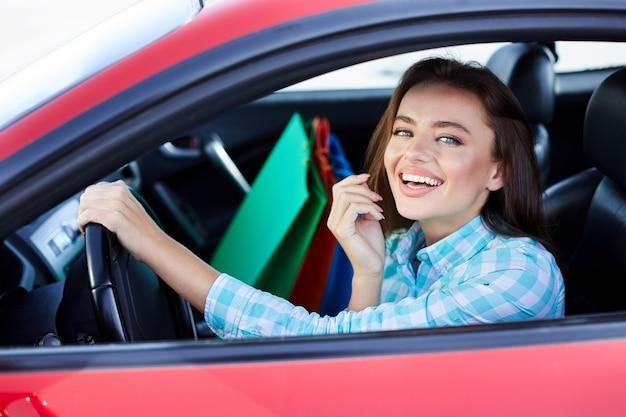 Frau sitzt im roten auto, glücklicher fahrer. frau, die kamera betrachtet und lächelt. kopf und schultern der glücklichen frau, die das ruder hält und vom einkaufen zurückkommt
