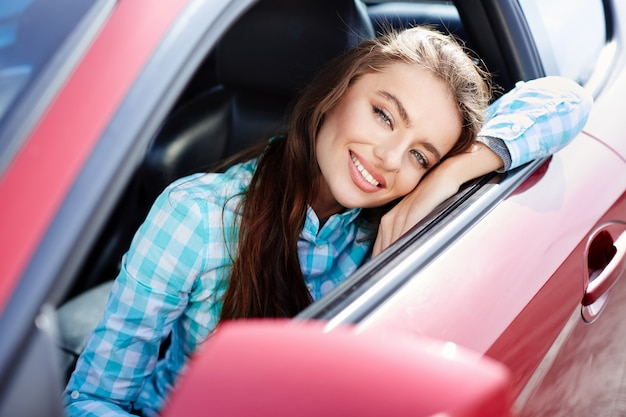 Frau sitzt im roten auto, glücklicher fahrer. frau, die kamera betrachtet und lächelt. kopf und schultern des glücklichen besitzers eines neuen autos, der sich auf das auto stützt und nach draußen schaut
