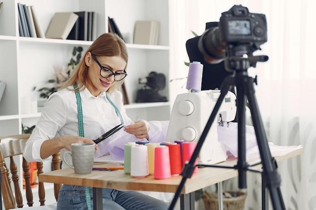 Frau sitzt im studio und näht stoff