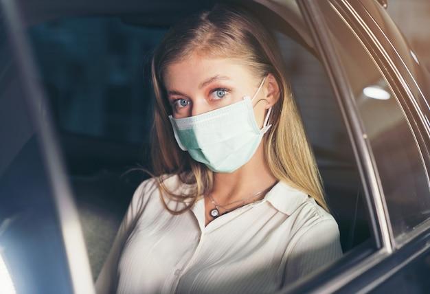 Frau sitzt im taxi mit einer maske
