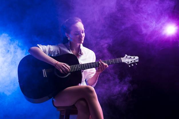 Frau sitzt in der klassischen position zum gitarrenspielen