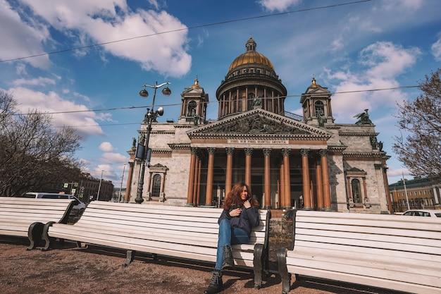 Frau sitzt in der nähe der isaakskathedrale in sankt petersburg im winter