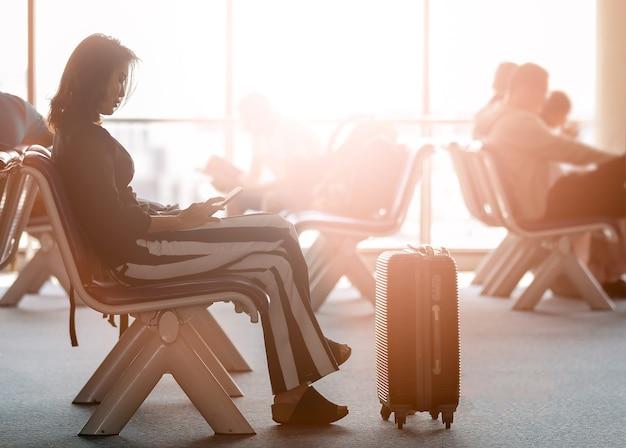 Frau sitzt in der nähe der reisetasche in der flughafenlobby mit smartphone und schaut auf den bildschirm, während sie auf den transit wartet. sonnenlicht, das von außen scheint.