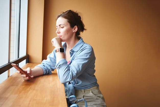 Frau sitzt in der nähe des fensters im café und benutzt ihr telefon. warten auf die bestellung
