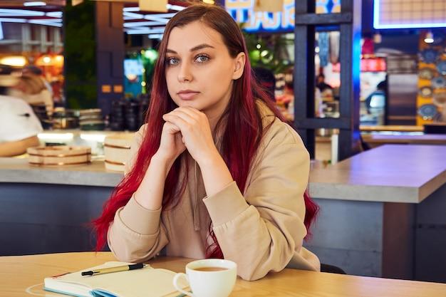 Frau sitzt in einem café mit einem offenen tagebuch mit einer tasse tee