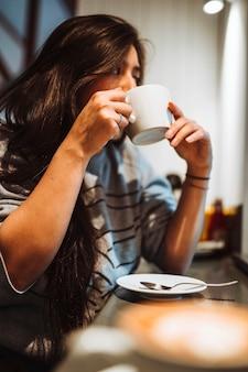 Frau sitzt in einem café und trinkt kaffee