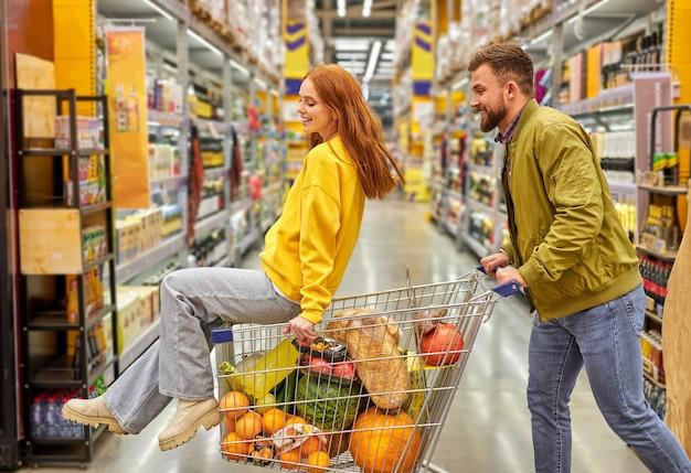 Frau sitzt in einem wagen voller essen, mann trägt den wagen. sorgloses verliebtes paar viel spaß beim einkaufen im supermarkt