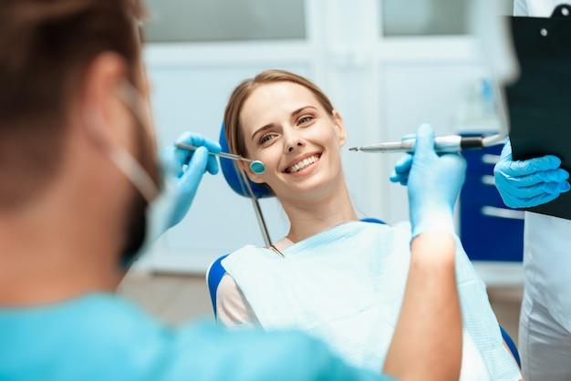 Frau sitzt in einem zahnarztstuhl. ärzte verneigten sich über sie.