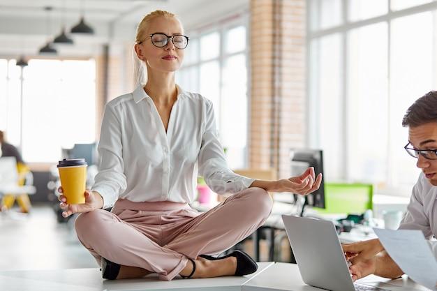 Frau sitzt in yoga-pose auf dem tisch bei der arbeit, meditiert alleine, bleibt ruhig, braucht etwas ruhe