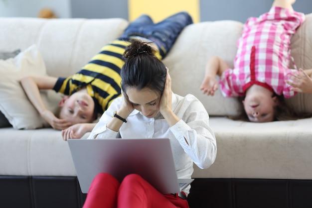 Frau sitzt mit einem laptop auf dem boden und hält sich mit den händen die ohren zu. hinter ihr auf der couch spielen kinder herum.