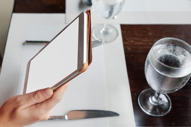 Frau sitzt mit einer tablette auf esstisch im restaurant