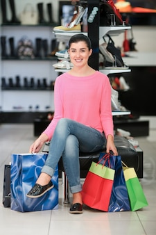 Frau sitzt mit einkaufstüten