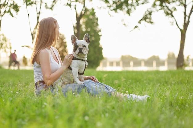 Frau sitzt mit französischer bulldogge auf gras