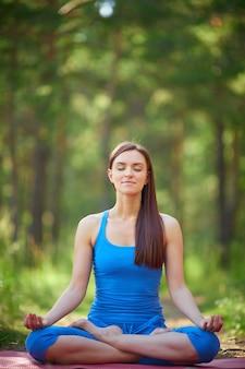 Frau sitzt mit gekreuzten beinen während der meditation