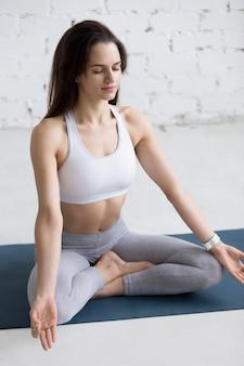 Frau sitzt mit gekreuzten beinen