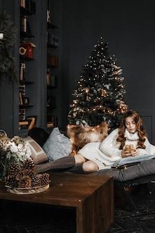 Frau sitzt mit kerzen am weihnachtsbaum.