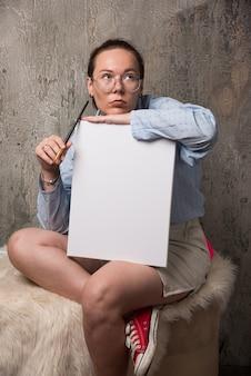 Frau sitzt mit leinwand und pinsel auf marmorhintergrund. hochwertiges foto Kostenlose Fotos