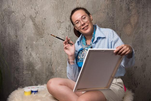 Frau sitzt mit leinwand und pinsel auf marmorhintergrund. hochwertiges foto