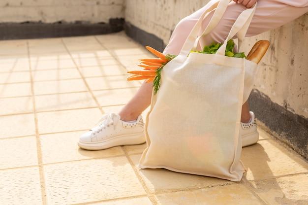 Frau sitzt mit wiederverwendbarer tasche