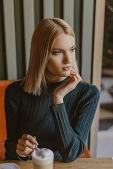 Frau sitzt morgens in einem café mit kaffee und croissant