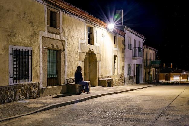 Frau sitzt nachts auf einer steinbank in einem alten dorf.