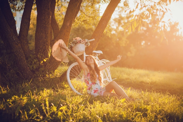 Frau sitzt neben dem fahrrad